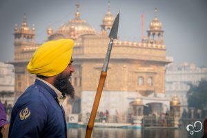 Imagem capturada durante Viagem à Índia de um guarda com uma lança em frente ao Templo Dourado em Amritsar, Índia