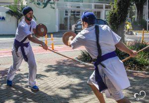 homens sikh usam turbantes enquanto lutam Gatka com bastões e escudos
